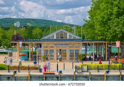 BALATONFURED, HUNGARY - JUNE 06, 2016: Building of port of resort town of Balatonfured, located at the coast of Balaton lake, at summer sunny day, and some people are walking.