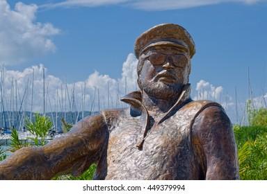BALATONFURED, HUNGARY - JUNE 2, 2016: Statue of Istvan Bujtor, Hungarian actor and enthusiast of sailing, is located at promenade of Balatonfured town, resort area of Balaton lake. Selective focus.