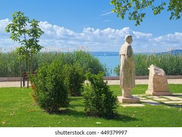 BALATONFURED, HUNGARY - JUNE 2, 2016: Statue of Sandor Petho, founder of newspaper Hungarian Nation, at promenade of Balatonfured town, with Balaton lake on the background.