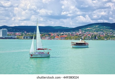 BALATONFURED, HUNGARY - JUNE 6, 2016: Yacht and touristic ship on Balaton lake, Hungary, are floating on clear water of emerald color and Balatonfured town is visible on the coastline.
