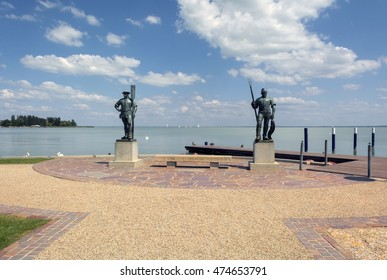 BALATONFURED,HUNGARY,-JULY 1. 2016.: The Fisherman and the Ferryman statues at the port of Balatonfured,with sailboats and swan in the background on Lake Balaton