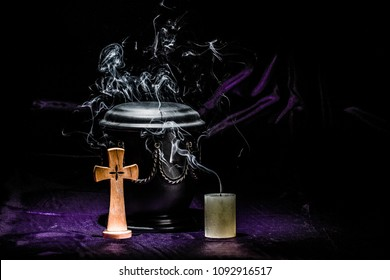 balck urn with golden decoration, cross, and smoky candle, raw for sympathy card