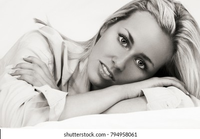 Balck and white studio shot of a beautiful young woman laying down relaxing on her bed
