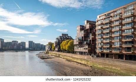 The balconies and facades of blocks of contemporary flats on the banks of the River Thames, London, on a bright autumnal day.