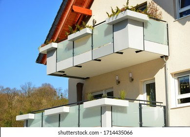 Balconies with Metal Hand Rails and combined privacy protection Screen of varnished plastic Planks and Glass and integrated Flower Boxes at the Front of a modern Multi Family Building
