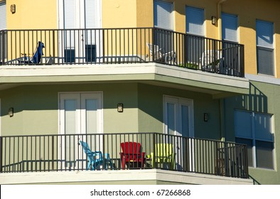 Balconies in pastel colors in bright sunlight with colorful chairs.