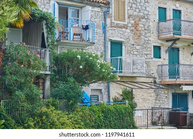 Balconies and shutters on a stone house facade in Vrsar, Croatia, decorated with flowers and green plants