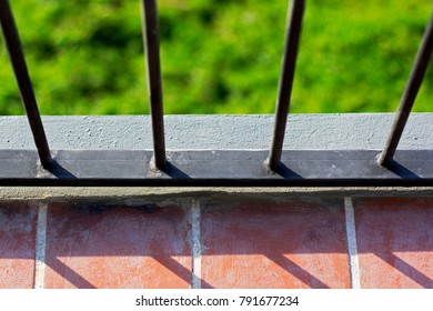Balcony with black metal fence and blurred green plant Background.