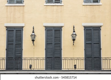 Balcony of a French Quarter (New Orleans, Louisiana) apartment, with doors and gas lamps.
