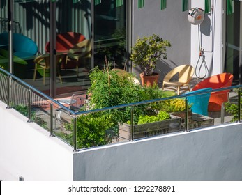A balcony with green plants growing in garden bed.