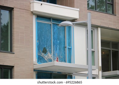 A balcony has been damaged and the glass pane broken by vandalism.