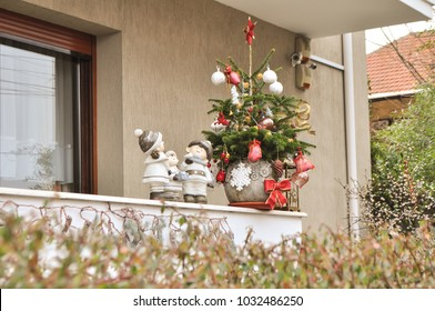 The balcony of the house is decorated for Christmas, with dwarfs and a decorated Christmas tree.