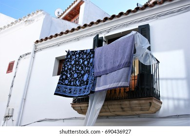 Balcony with Indian scarves lying in Ibiza,House facade white in historic center of Ibiza, house of ibiza, Spain., , cobbled streets and steep,narrow streets