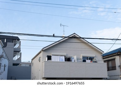 A balcony of a Japanese house has clothes hanging outside on the poles