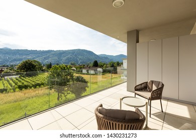 Balcony with outdoor furniture in luxury house. Nature view. Nobody inside