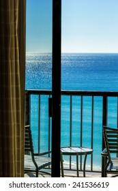 Balcony overlooking Gulf of Mexico in Destin, Florida through sliding glass door.