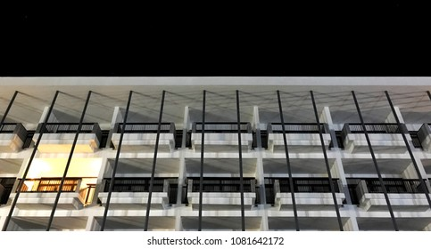 balcony pattern of low rise hotel building exterior with dark night sky background, lighting at room terrace with steel fence and pole, low angle view from outdoor, no people, feel lonely emotion