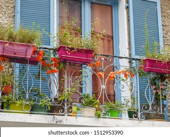 Balcony with its rails decorated with plants and colorful planters, large rectangular windows with blue painted shutters of a building's facade in Lourdes, Hautes-Pyrenees, Occitanie, Southwest France