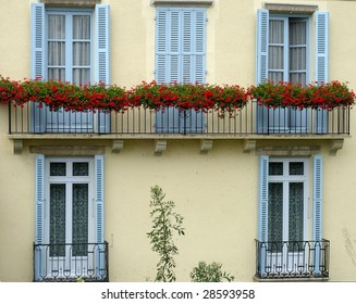 Balcony with red flowers on old house, blue windows and yellow wall