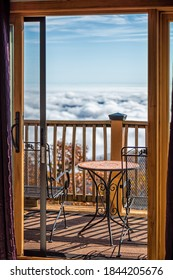 Balcony terrace outside in Wintergreen, Virginia with blue ridge mountain view and cloud inversion with blue sky and sunlight on chairs table railing