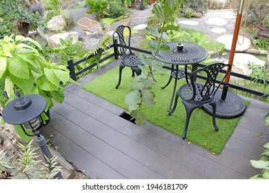 Balcony or terrace with set of black metal table and chairs overlooking a green landscaped tropical garden