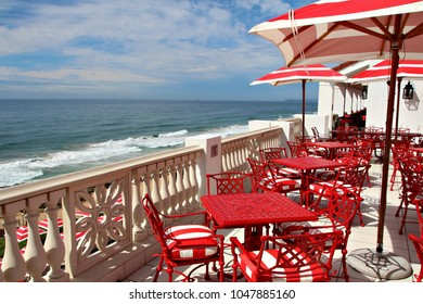 A balcony or verandah with red chairs and tables looks out over a beautiful blue ocean.
