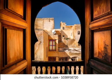 Balcony view of Arab building and window. Rustic balcony doors and view in the Medina of Fes, Morocco. Famous example of Moroccan architecture and a popular tourist sight