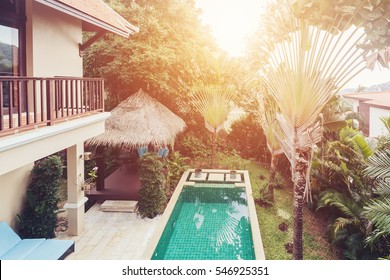 Balcony View of swimming pool and palm trees in luxury villa garden