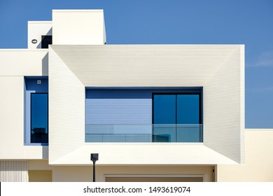 Balcony of a white and blue modern villa in a Middle Eastern, high-end, luxury housing development on a sunny day with strong shadows.