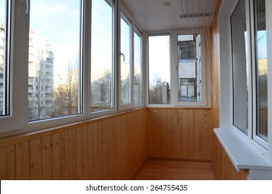 Balcony with the windowed parapet after reconstruction. Interior of a balcony made with tinted pine paneling