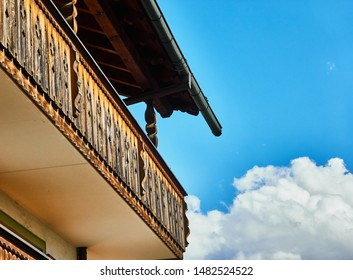 Balcony of wood and eaves of a traditional Bavarian house in front of a blue and white sky