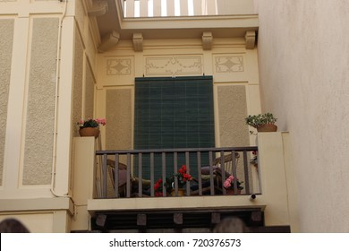 Balcony with wooden rail fence and two rocking chairs and flowers. Two wooden armchairs in a balcony