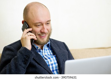 Bald adult man with a beard in a jacket using a smart phone and computer. Business man sitting, working and talking on mobile phone, looking at laptop screen. Mobile office and workspace concept.