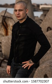 Bald attractive man in tattoos on the ocean. Tattooed brutal young man stands on the ocean in a black denim jacket. A stern guy posing while on the coastline by the sea. Stylish and fashionable guy.