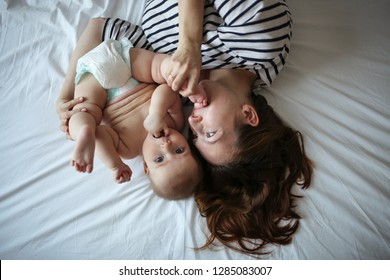 Bald baby and funny mom with flowing hair hugging on the bed, concept of motherhood and tenderness, kisses and toning