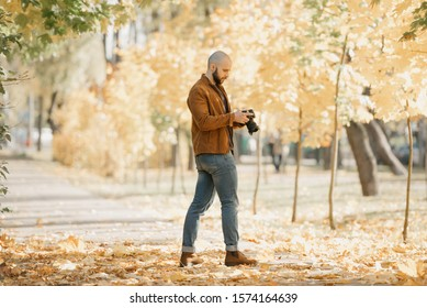 Bald brutal half-turn photographer with a beard in a suede leather jacket, blue shirt, jeans, and Chelsea boots scrolls photos on the camera in the park in the afternoon