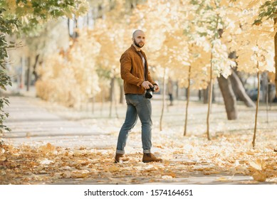 Bald brutal half-turn photographer with a beard in a suede leather jacket, blue shirt, jeans, and Chelsea boots holds the camera and waits for a model in the park in the afternoon