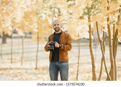 Bald brutal photographer with a beard in a suede leather jacket, blue shirt and jeans holds the camera and smiles in the park in the afternoon