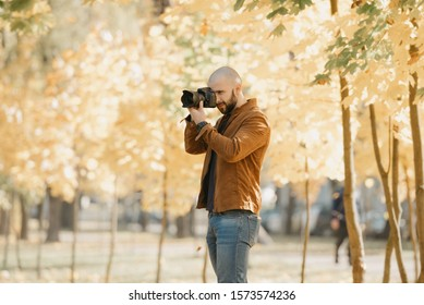 Bald brutal photographer with a beard in a suede leather jacket, blue shirt and jeans photographs in the park in the afternoon