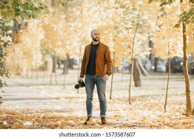Bald brutal photographer with a beard in a suede leather jacket, blue shirt, jeans, and Chelsea boots looks for somebody in the park in the afternoon