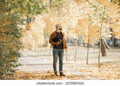 Bald brutal photographer with a beard in a suede leather jacket, blue shirt, jeans and chelsea boots holds the camera and looks around in the park in the afternoon