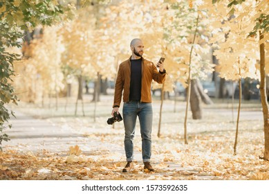 Bald brutal photographer with a beard in a suede brown leather jacket, blue shirt, jeans, and Chelsea boots holds a camera and a smartphone in the park in the afternoon