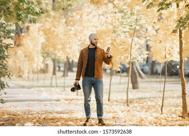 Bald brutal photographer with a beard in a suede leather jacket, blue shirt, jeans, and Chelsea boots holds a camera and a smartphone in the park in the afternoon