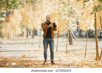 Bald brutal photographer with a beard in a suede leather jacket, blue shirt, jeans, and Chelsea boots scrolls photos on the camera in the park in the afternoon