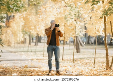 Bald brutal photographer with a beard in a suede leather jacket, blue shirt, jeans, and Chelsea boots photographs in the park in the afternoon