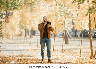 Bald brutal photographer with a beard in a suede leather jacket, blue shirt, jeans, and Chelsea boots goes to take a picture in the park in the afternoon
