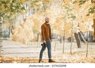 Bald brutal photographer with a beard in a suede leather jacket, blue shirt, jeans, and Chelsea boots holds the camera and waits for a model in the park in the afternoon
