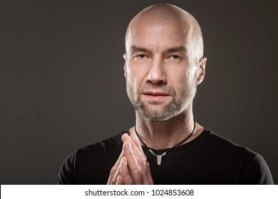 Bald, brutal stylish man praying