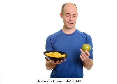 Bald Caucasian man  choosing between bowl of potato chips and green apple isolated against white background