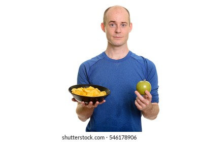 Bald Caucasian man  holding bowl of potato chips and green apple isolated against white background